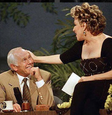 On This Day In History: Entertainer Bette Midler caresses talk show host Johnny Carson